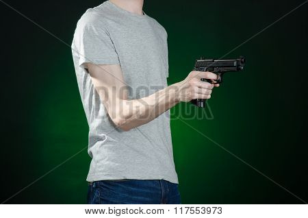 Firearms And Murderer Topic: Man In A Gray T-shirt Holding A Gun On A Dark Green Background Isolated