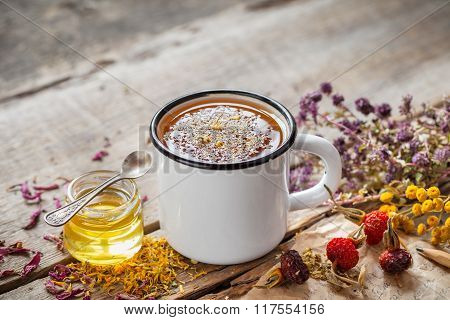 Cup Of Healthy Daisy Tea, Honey And Healing Herbs On Table. Herbal Medicine.