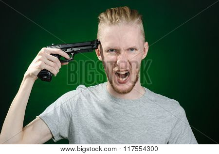 Firearms And Murderer Topic: Suicide In A Gray T-shirt Holding A Gun On A Dark Green Background Isol