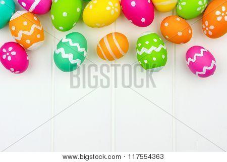 Easter egg top border against white wood