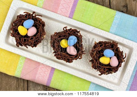 Chocolate nests with candy eggs on colorful Easter table cloth