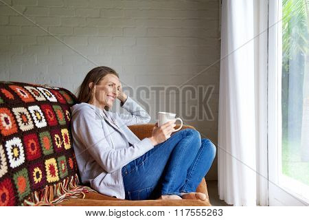 Smiling Older Woman Relaxing At Home With Cup Of Tea
