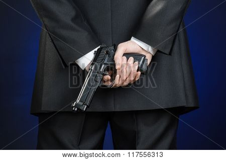 Firearms And Security Topic: A Man In A Black Suit Holding A Gun On A Dark Blue Background In Studio