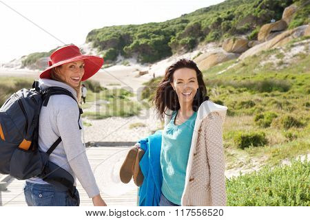 Two Women Friends Walking To The Beach With Bag And Clothes