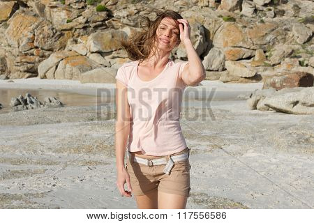 Beautiful Woman Walking On Beach With Hand In Hair