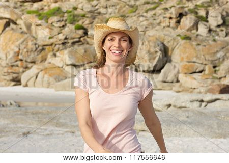 Smiling Older Woman Walking At The Beach With Hat
