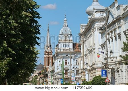 ARAD, ROMANIA - JULY 30, 2015: domes and bell tower of University Aurel Vlaicu and City Hall Palace along Revolution Avenue of Arad.
