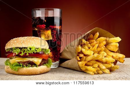 Cheeseburger With Drink Of Cola And French Fries On Red Spotlight