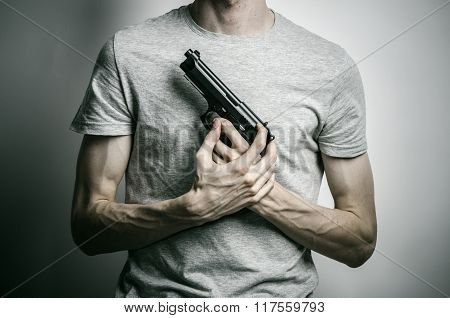 Horror And Firearms Topic: Suicide With A Gun On A Gray Background In The Studio