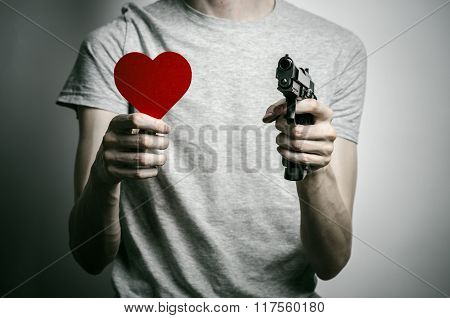 Horror And Firearms Topic: Suicide With A Gun In His Hand And A Red Heart On A Gray Background In Th