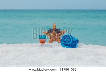Starfish, towel and cocktail on white sand tropical beach