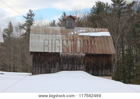 A weathered stained barn in winter
