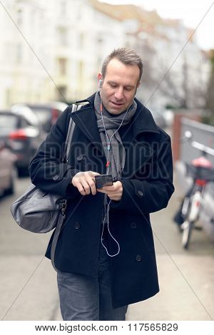 Attractive Man Checking His Mobile In A Street
