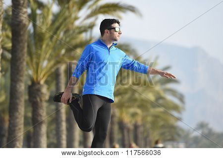 Runner Man  Stretching At Beach Palm Trees Boulevard With Sunglasses In Morning Jog Training Session