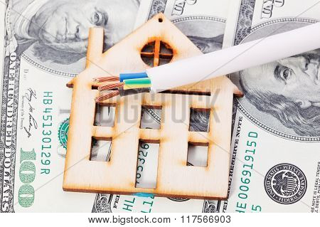 Model Of Wooden House With Dollar Bills And Electric Cable. House Building, Loan, Real Estate, Cost