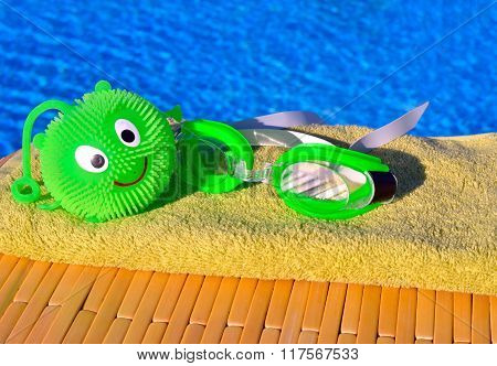 Bath Towels, Goggles, Toy Against Blue Water.