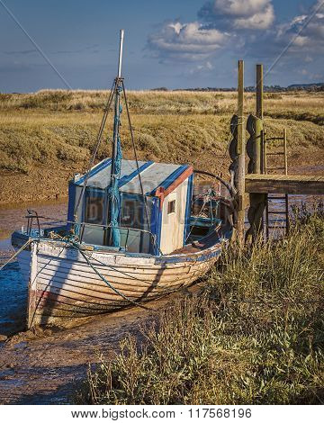 Old decaying wooden fishing boat moored up