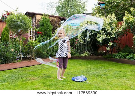 Girl Playing With Soap Bubbles In Beautiful Garden