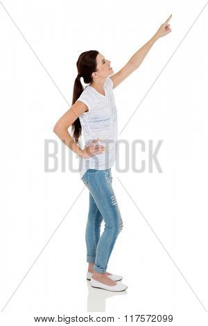 side view of pretty teen girl pointing on white background