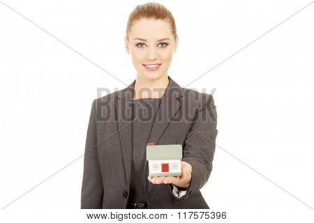 Businesswoman holding model house.