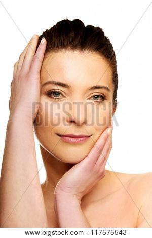 Spa woman with make up touching her face.