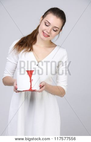 girl in white dress holding paint can