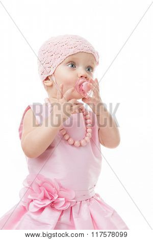 little child baby girl in pink dress with baby's dummy isolated on white studio shot