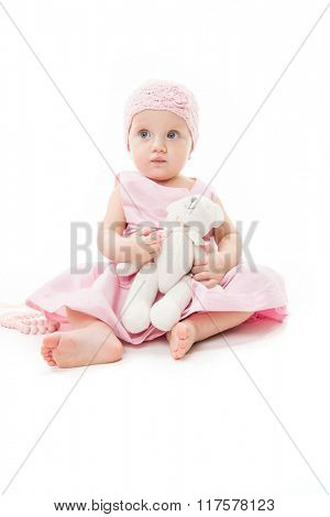 little child baby girl 1 year pink dress hat baby's dummy soother isolated on white studio shot playing with teddy bear