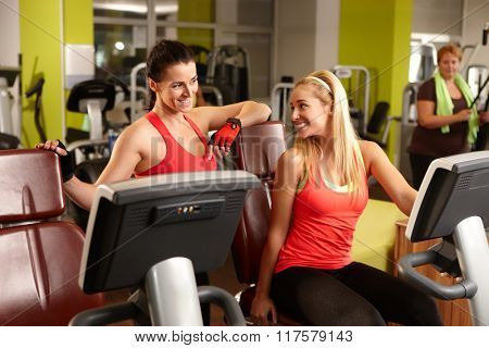 Two fit women talking in gym, exercising.