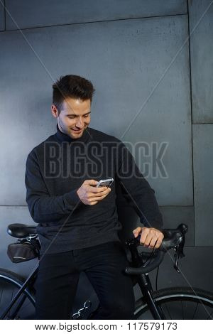 Young man leaning against bicycle holding mobilephone.