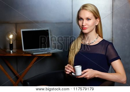 Portrait of elegant nordic type businesswoman having coffee-break, looking away.