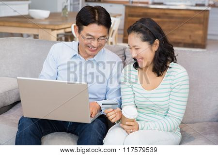 Happy couple shopping online on the sofa