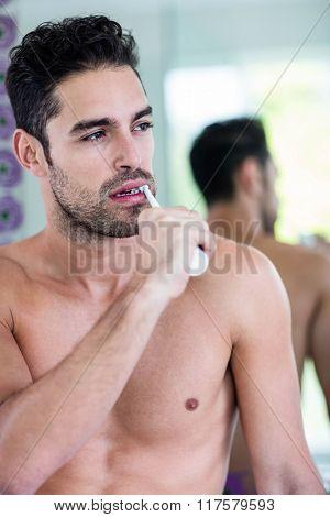 Handsome man brushing his teeth in bathroom