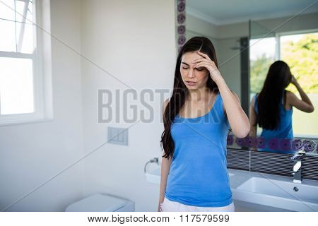 Pretty woman with headache in blue in bathroom