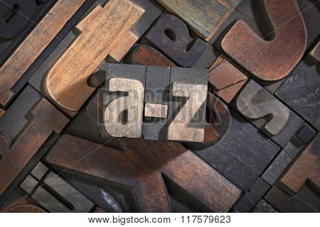 a-z written with letterpress printing blocks on random letters background