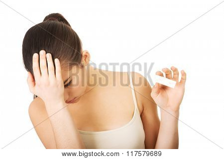 Depressed woman with pregnancy test.