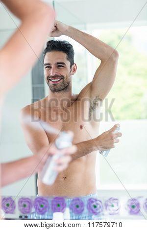 Handsome man using spray deodorant in bathroom