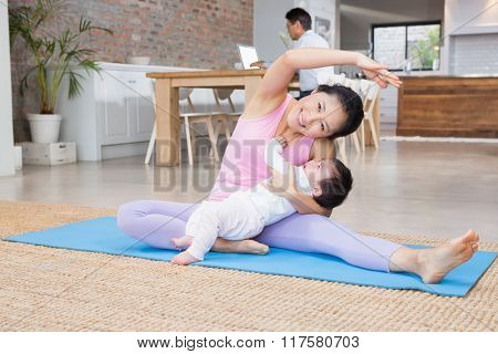 Happy mother and baby daughter exercising on mat at home