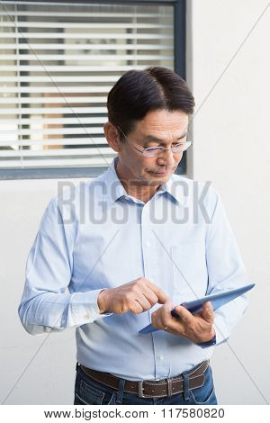 Serious man using tablet in his garden