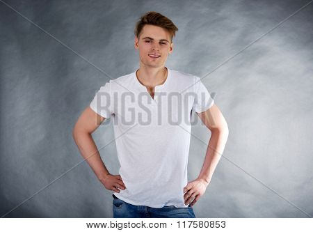Young smiling man with hands on hips.