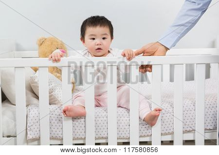Cute baby looking up from crib at home in bedroom