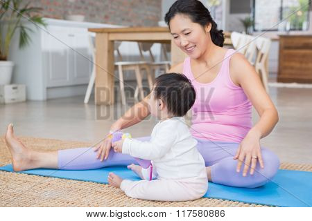 Happy mother exercising on mat while looking at baby daughter at home