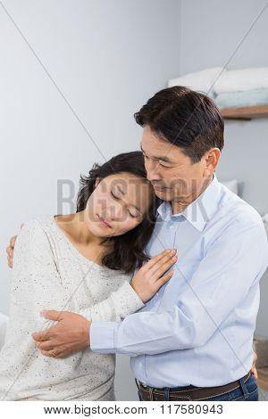 Sad couple embracing at home