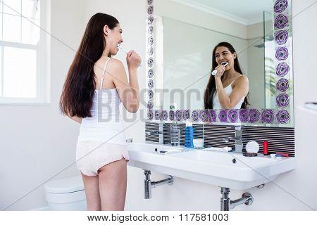 Brunette brushing teeth in bathroom
