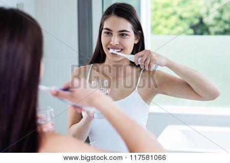 Smiling brunette brushing teeth in bathroom