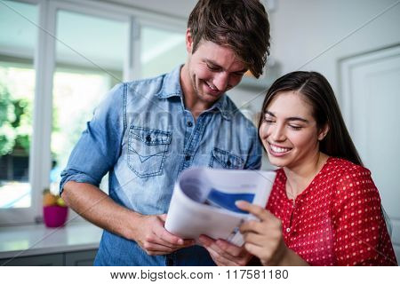 Happy couple reading newspaper at home