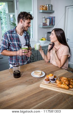 Happy couple having breakfast together at home