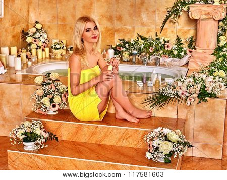 Woman relaxing at water spa. Girl sitting near a bath tub on stair.