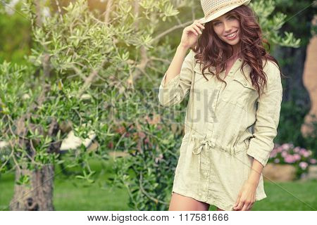 Beautiful Young Woman Outdoor. Enjoy Nature. Healthy Smiling Girl in the garden. Sunny day