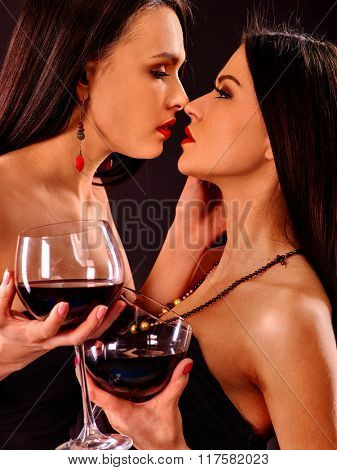 Lesbian women drinking red wine and kissing on nightclub.